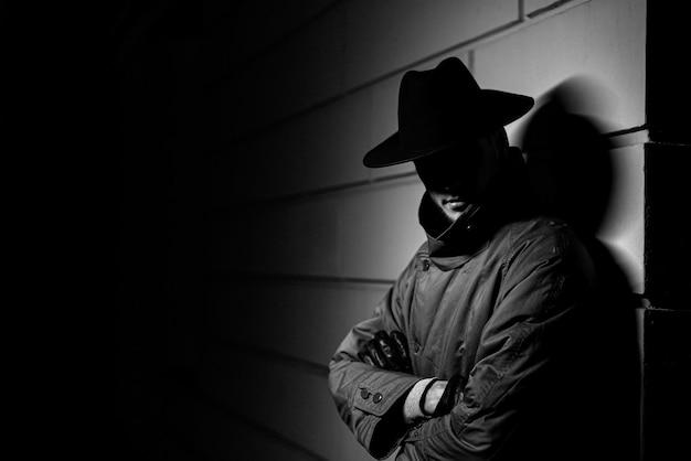 Retrato escuro de um homem com capa de chuva e chapéu à noite na rua em estilo crime noir