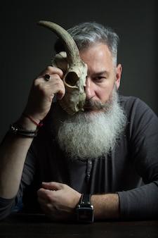 Retrato escuro de um homem de meia idade barbudo com uma caveira animal