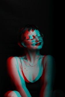 Retrato escuro de uma garota sexy sentada em uma cadeira. ruído é sobreposto na foto preto e branco com efeito de falha