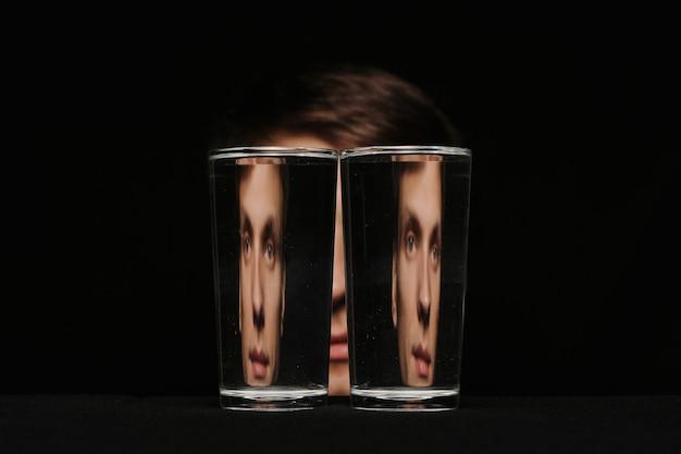 Retrato estranho de um homem olhando através de dois copos d'água