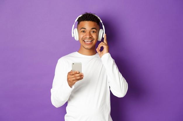 Retrato expressivo de jovem segurando o celular e ouvindo música