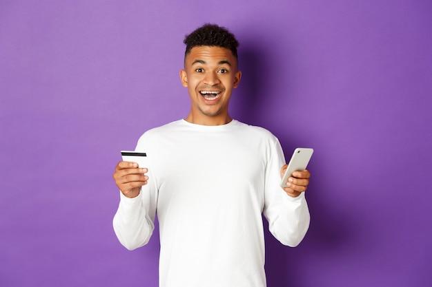 Retrato expressivo de jovem segurando o telefone e o cartão de crédito