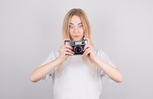 Retrato expressivo de uma bela jovem loira surpresa em uma camiseta branca com uma câmera nas mãos