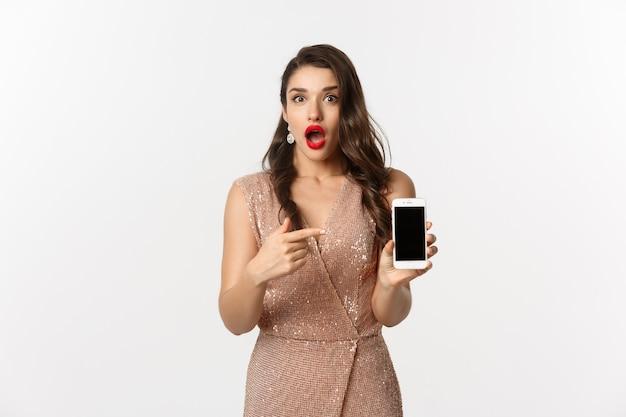 Retrato expressivo jovem em um vestido elegante segurando o telefone