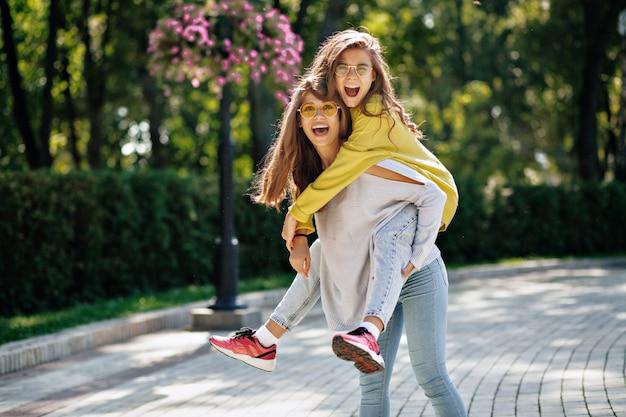 Retrato externo de duas garotas adoráveis se divertindo brincando e rindo juntas na rua, tolo, pular, ter um bom humor na cidade