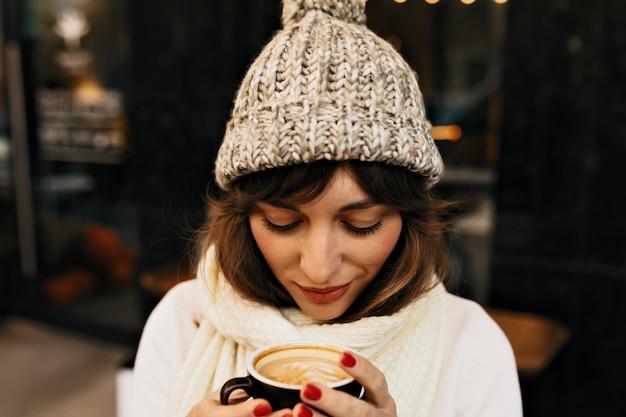 Retrato externo de uma garota muito charmosa com café, vestindo boné de inverno e suéter branco em luzes.
