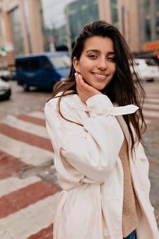 Retrato externo de uma mulher atraente com cabelo escuro e jaleco branco caminhando na rua com um sorriso encantador