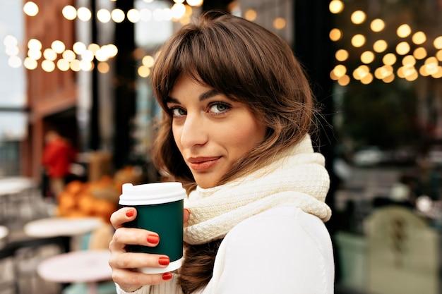 Retrato externo de uma mulher bonita e encantadora com cabelo escuro, vestindo uma blusa de malha branca, bebendo café no fundo de luzes