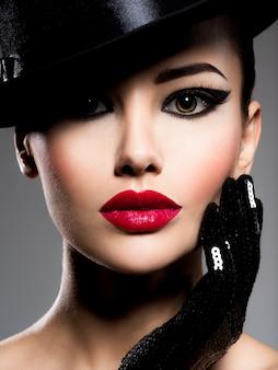 Retrato fechado de uma mulher em um chapéu preto e luvas com lábios vermelhos posando