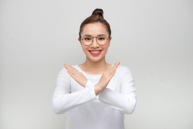 Retrato feliz asiática linda jovem confiante segurando dois braços cruzados e dizendo que não há sinal de x na parede branca