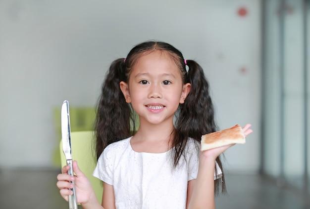 Retrato feliz criança menina cozinhando na sala de aula. as crianças mostram uma geléia de morango no pão.