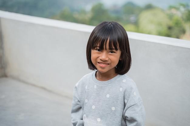 Retrato feliz de uma menina de férias em um café desfrutando de um sorriso