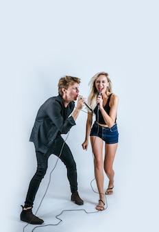 Retrato feliz do casal segurando o microfone e cantar uma canção
