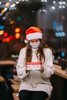 Retrato feliz, jovem e bonita segurando uma caixa de presente e sorrindo no café