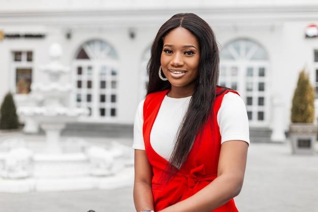 Retrato feliz jovem negra com uma pele limpa, saudável com um sorriso positivo, com belos olhos em roupas vermelhas da moda, ao ar livre na cidade. modelo alegre sorridente garota africana é relaxa na rua.