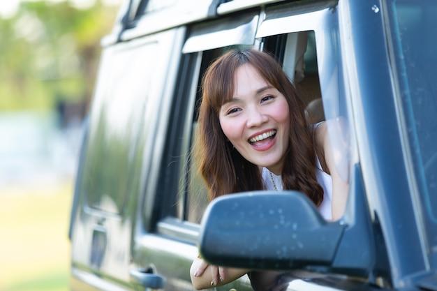 Retrato feliz mulher asiática dirige uma velha van vintage campista na estrada. viagem de férias em família