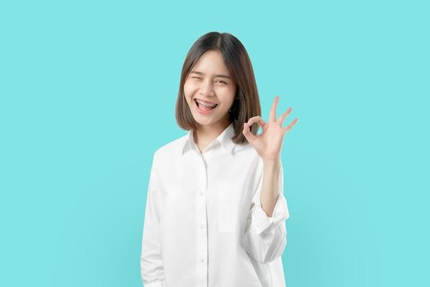 Retrato feliz mulher asiática mostra sinal de ok e aparelho sorrindo bruxa olhando para a câmera