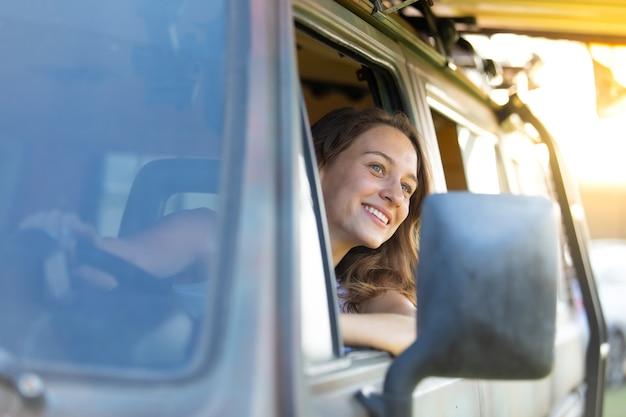 Retrato feliz mulher caucasiana dirige uma velha van vintage campista na estrada. viagem de férias em família