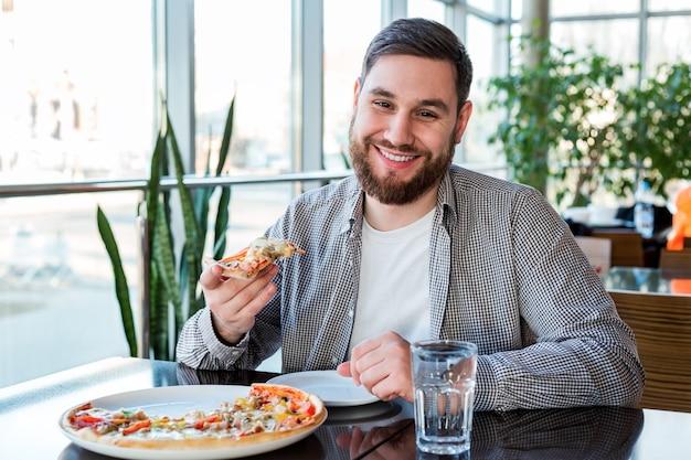 Retrato feliz sorridente homem caucasiano comendo pizza italiana na pizzaria mantém distância social. pizza deliciosa no café.