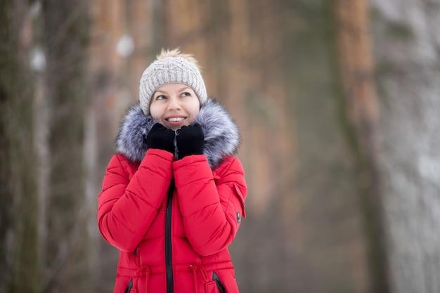 Retrato feminino ao ar livre em casaco de inverno vermelho