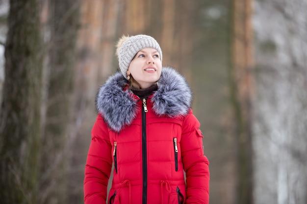 Retrato feminino ao ar livre no inverno jaqueta vermelha brilhante