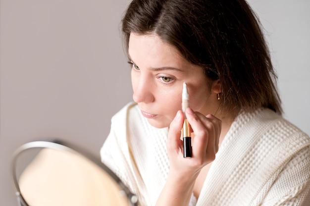 Retrato feminino aplicando olho concelear
