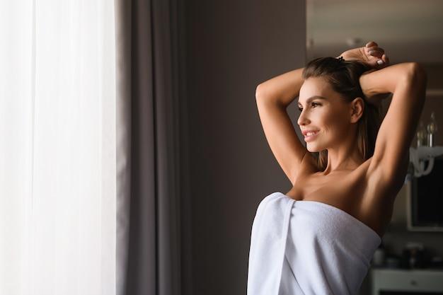 Retrato feminino atraente com as mãos levantam, alongamento de manhã no apartamento depois do spa, banho, na luz da manhã linda. feliz senhora sexy envolto em uma toalha branca dentro de casa.