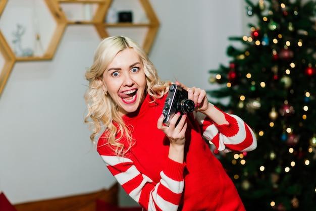 Retrato feminino com um lindo sorriso e cachos no cabelo loiro. mulher segura fotógrafa da senhora da câmera.