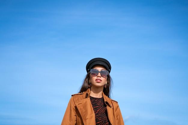 Retrato feminino de uma bela jovem de aparência caucasiana em um boné preto contra um céu azul.