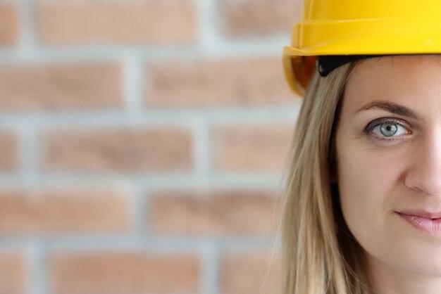 Retrato feminino do construtor com capacete amarelo contra o fundo da parede