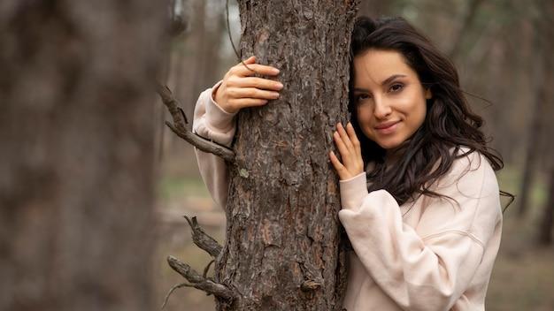 Retrato feminino na natureza, abraçando a árvore