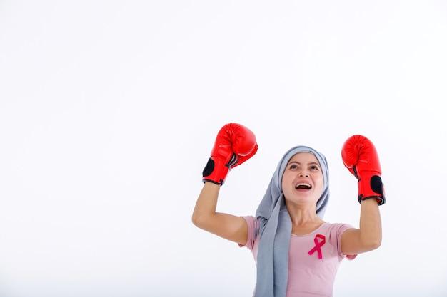 Retrato forte de uma mulher asiática lutando mostrando luvas de boxe mês de conscientização do câncer de mama isolado no fundo do estúdio de espaço de cópia em branco branco, conceito de saúde