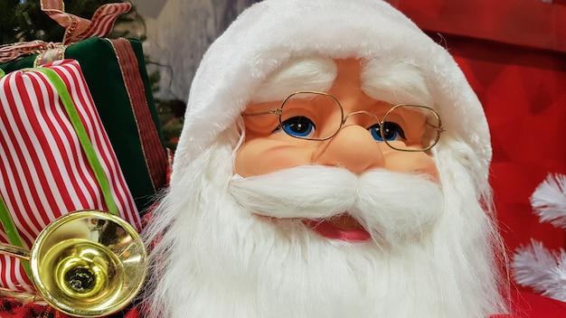 Retrato fotográfico de um feliz boneco de brinquedo papai noel com uma sacola de presentes simboliza a chegada do natal e do ano novo. clima festivo, conceito de férias.