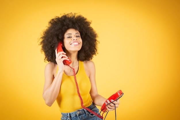 Retrato fotográfico de uma mulher de pele negra surpresa com cachos segurando dois telefones retrô