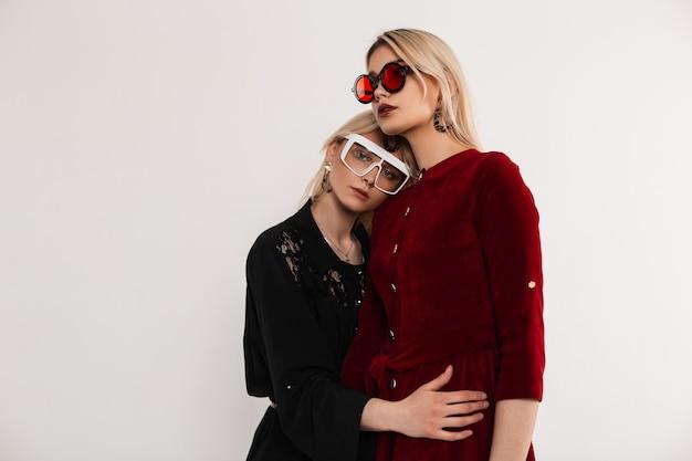 Retrato fresco jovem atraente loira irmãs mulheres em elegantes vestidos da moda vermelho e preto com óculos perto da parede cinza vintage no quarto