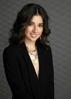 Retrato frontal da jovem morena sorridente com maquiagem, vestida com fundo cinza isolado de jaqueta preta.