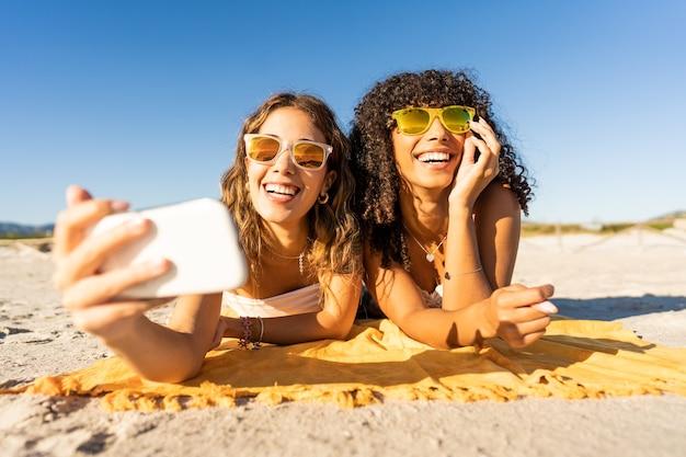 Retrato frontal de duas lindas garotas com óculos de sol nas férias de verão usando smartphone tirando uma selfie