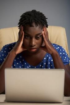 Retrato frontal de mulher negra frustrada com más notícias do pc portátil