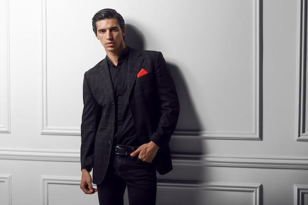 Retrato frontal de um homem de negócios carrancudo em um terno preto com lenço de seda vermelho no bolso, sobre fundo branco.