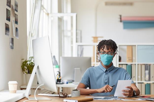 Retrato frontal de um jovem fotógrafo afro-americano usando máscara enquanto analisa fotos sentado na mesa em um estúdio caseiro, copie o espaço