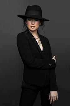 Retrato frontal de uma jovem esplêndida mulher morena de terno preto e chapéu com maquiagem, com os olhos fechados, sobre fundo cinza.