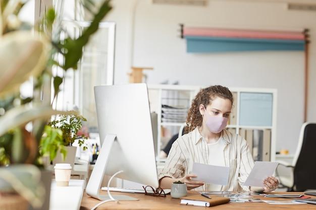 Retrato frontal de uma jovem fotógrafa usando máscara enquanto analisa as fotos sentado na mesa em um estúdio caseiro, copie o espaço