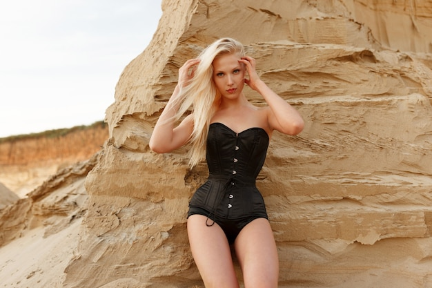 Retrato frontal de uma jovem mulher com cabelos loiros e maquiagem, vestida com uma roupa preta sexy, perto de uma parede de areia no deserto.