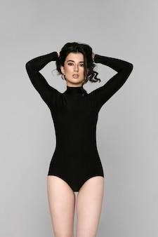 Retrato frontal de uma linda menina com cabelos cacheados morena e maquiagem, em uma roupa preta posando no estúdio, plano de fundo cinza. visão vertical.