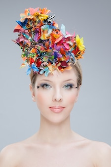 Retrato frontal de uma menina bonita, vestindo no topo da cabeça um buquê de flores