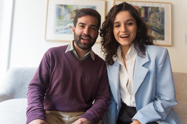 Retrato frontal do casal feliz dizendo oi na tela do gadget