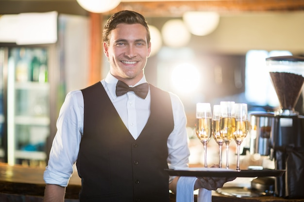 Retrato, garçom, segurando, servindo, bandeja, champanhe, flautas