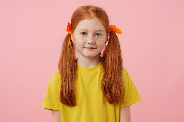 Retrato garotinha ruiva de sardas com duas caudas, olha para a câmera e sorri, usa uma camiseta amarela, fica sobre um fundo rosa.