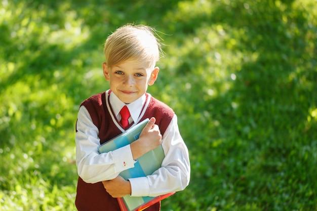 Retrato garotinho na natureza. criança com livros e uniforme vestido. educação para crianças. volta ao conceito de escola.
