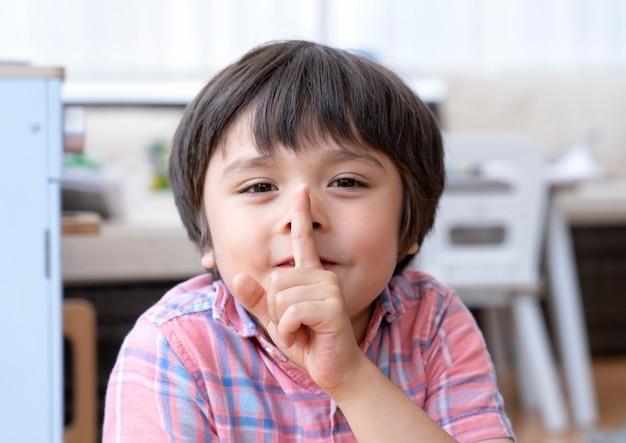 Retrato garoto garoto feliz sentado na sala de jogos, mostrando o dedo nos lábios símbolo do gesto de silêncio